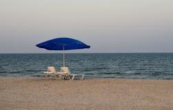 Öde strand med deckchairs och slags solskydd Arkivfoton
