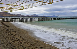 Öde strand, pir i dåligt väder Arkivbilder