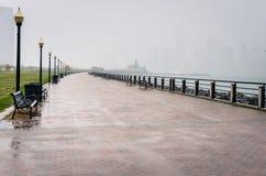 Öde strandvandringsled under hällregn arkivbilder