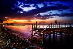 Ödelagd skeppsdocka på solnedgång med det lugna havet arkivbild