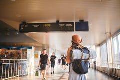 Öffentliche Transportmittel der Themareise Stellung der jungen Frau mit Rückseite im Kleid und im Hut hinter Rucksack und kampier stockfotografie