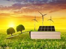 Öffnen Sie ökologisches Buch mit Sonnenkollektor und Windkraftanlage auf Wiese bei Sonnenuntergang stockbilder