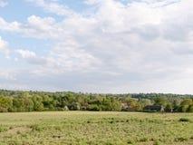 Öffnen Sie Ackerland mit Häusern im Abstand draußen im Land Lizenzfreies Stockfoto