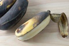 Öffnen Sie alte Bananen-Frucht auf hölzernem Brett Stockbilder