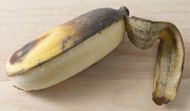 Öffnen Sie alte Bananen-Frucht auf Holztisch Stockbilder