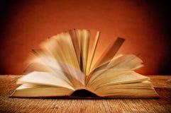 Öffnen Sie altes Buch auf einem rustikalen Holztisch Stockbild