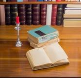 Öffnen Sie altes Buch und Stapel einiger Bücher durch Kerzenlicht Lizenzfreie Stockfotos