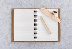 Öffnen Sie Anmerkungsbuch mit Stift, hölzernem Machthaber und Bleistiftspitzer Lizenzfreie Stockfotos