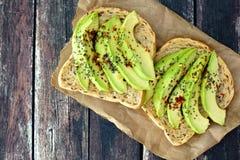 Öffnen Sie Avocadosandwiche auf Papier gegen rustikales Holz stockfoto