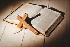 Öffnen Sie Bibel und hölzernes Kreuz Stockfotos