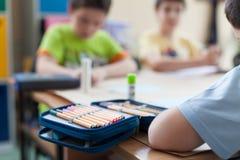 Öffnen Sie Bleistiftkasten auf hölzernem Klassenzimmer Stockbilder