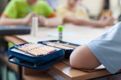 Öffnen Sie Bleistiftkasten auf hölzernem Klassenzimmer Stockfotografie