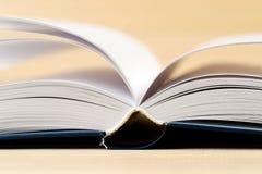 Öffnen Sie Buch auf hölzerner Tabelle Stockbild