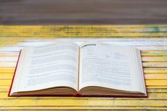 Öffnen Sie Buch auf hölzerner Tabelle Stockbilder