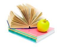 Öffnen Sie Buch, einen Stapel Notizbücher und einen Apfel Stockfotos