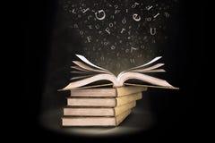 Öffnen Sie Buch mit den Zeichen, die in die Seiten fallen Stockbilder