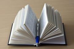 Öffnen Sie Buch und Stift Stockfotografie
