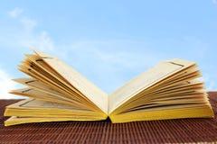 Öffnen Sie das alte Buch, das auf Himmelhintergrund lokalisiert wird Lizenzfreie Stockfotografie