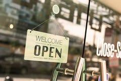 Öffnen Sie das Zeichen, das durch das Glas des Fensters an der Kaffeestube breit ist stockbild