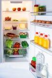 Öffnen Sie den Kühlschrank, der mit Lebensmittel gefüllt wird lizenzfreies stockfoto