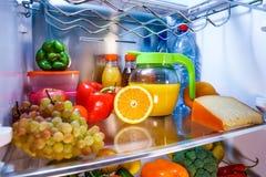 Öffnen Sie den Kühlschrank, der mit Lebensmittel gefüllt wird stockbilder