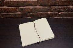 Öffnen Sie den Notizblock oder Sketchbook, die auf schwarzem Hintergrund liegen stockfotografie