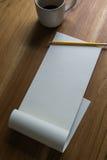 Öffnen Sie Diagrammauflage mit Bleistift und einem Tasse Kaffee auf einem hölzernen Schreibtisch Stockfotografie