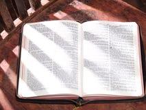 Öffnen Sie die Bibel, die auf altem hölzernem Sunlit Stuhl sitzt Stockfoto