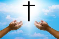 Öffnen Sie die Hände, die das Kreuz auf Unschärfehimmelhintergrund beten Stockbild