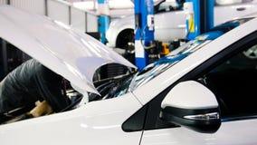 Öffnen Sie die Haube von dem Motor- die Maschine, die Batterie, der Injektor - der Mechaniker, der im Automobilservice arbeitet lizenzfreies stockbild