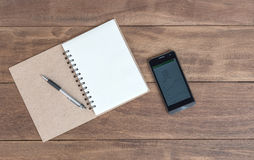 Öffnen Sie ein leeres Notizbuch, einen Stift und einen Handy Stockbilder