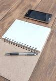 Öffnen Sie ein leeres Notizbuch, einen Stift und einen Handy Lizenzfreie Stockfotografie