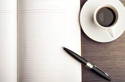 Öffnen Sie ein leeres weißes Notizbuch, einen Stift und einen Kaffee auf dem Schreibtisch Stockbild