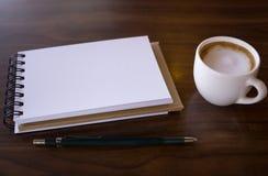 Öffnen Sie ein leeres weißes Notizbuch mit heißem Kaffee auf Tabelle lizenzfreie stockfotos