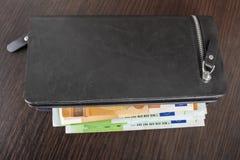 Öffnen Sie Geldbörse mit Eurobargeld 10 20 50 100 auf einem hölzernen Hintergrund Männer ` s Geldbörse mit Bargeldeuro Lizenzfreie Stockfotos