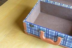 Öffnen Sie Gepäck auf Holztisch Stockfotos