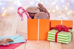 Öffnen Sie Geschenk auf Holztisch und Buchstaben Stockfoto