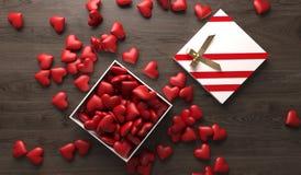 Öffnen Sie Geschenkbox voll Herzen auf dunkler Holzoberfläche Stockfotos