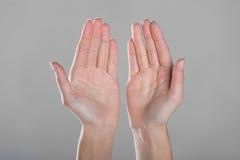 Öffnen Sie Hände auf grauem Hintergrund Stockfotos