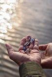 Öffnen Sie Hand mit religiöser Queraußenseite durch See bei Sonnenuntergang mit funkelndem Wasser stockfotografie