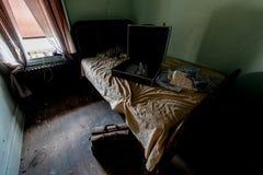 Öffnen Sie Koffer auf unordentlichem Bett - verlassene Catskills-Gebirgswohnung, New York Stockbilder