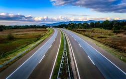 Öffnen Sie Landstraße durch Hirtenlandschaft Stockbilder