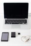 Öffnen Sie Laptop mit schwarzem Smartphone Lizenzfreie Stockfotografie