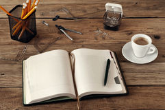 Öffnen Sie leeres Notizbuch auf einem hölzernen Schreibtisch mit einer Schale schwarzem Kaffee, Stockfotos