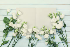 Öffnen Sie leeres Notizbuch und Blumenstrauß von weiße Blumen Eustoma auf blauer rustikaler Tischplatteansicht Frauenarbeitsschre Lizenzfreie Stockbilder