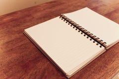 Öffnen Sie Leerseiten des Notizbuches auf Holztischweinleseart Stockfoto