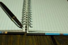 Öffnen Sie Leerseitennotizbuch und -stift auf einem rustikalen hölzernen Schreibtisch Ein strukturierter Hintergrund Kopieren Sie Lizenzfreie Stockfotografie