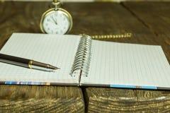 Öffnen Sie Leerseitennotizbuch und -stift auf einem rustikalen hölzernen Schreibtisch Ein strukturierter Hintergrund Kopieren Sie Stockfotografie