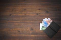 Öffnen Sie männliche schwarze lederne Geldbörse mit Eurorechnungen auf Holz Stockfotografie