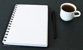 Öffnen Sie Notizblock und Tasse Tee Stockbild